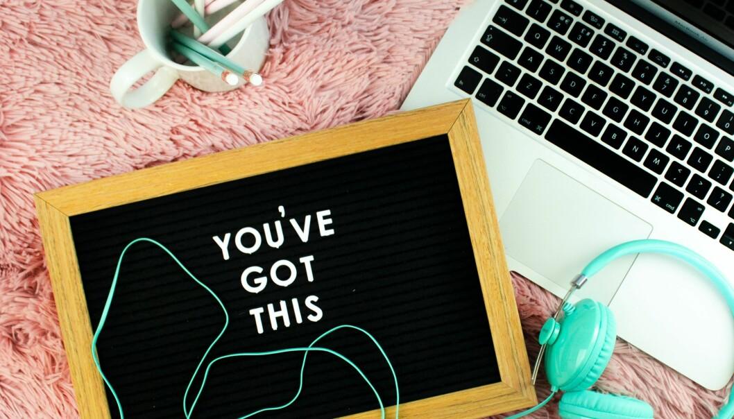 En dator, pennor, hörlurar och en skylt som försöker sprida lite glädje och styrka under coronapandemin.