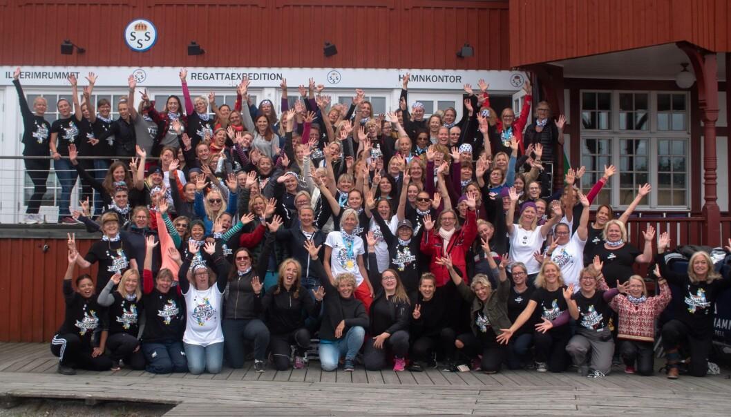 130 kvinnor aktiva i nätverket She Captain framför ett hamnkontor i Stockholms skärgård.