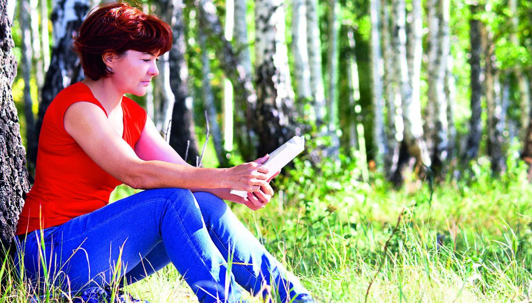 Kvinna sitter och läser i gräset