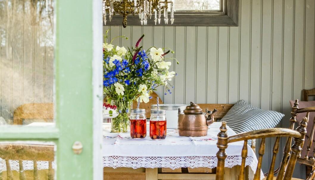 Träbord med vit duk, dukat med saft i burkar, en kopparkittel och glasvas med sommarblommor, ljusgrön träpanel i bakgrunden och kristallkrona i taket.