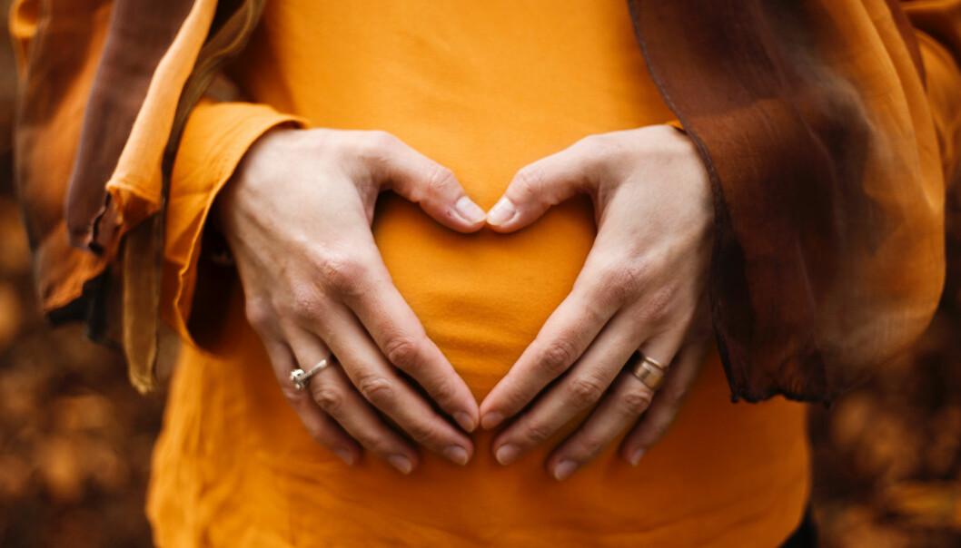 Blivande mamma formar hjärta med händerna på magen