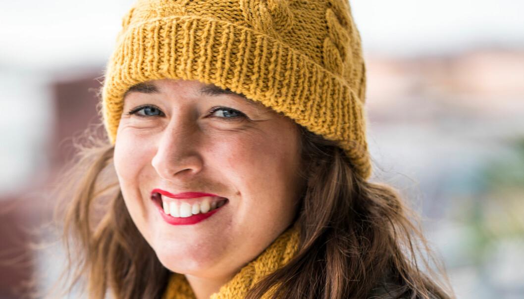 Kvinna i stickad gul mössa med matchande halsduk