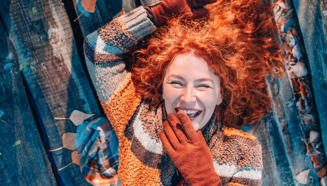 Glad kvinna med rött hår ligger på ett träbrygga