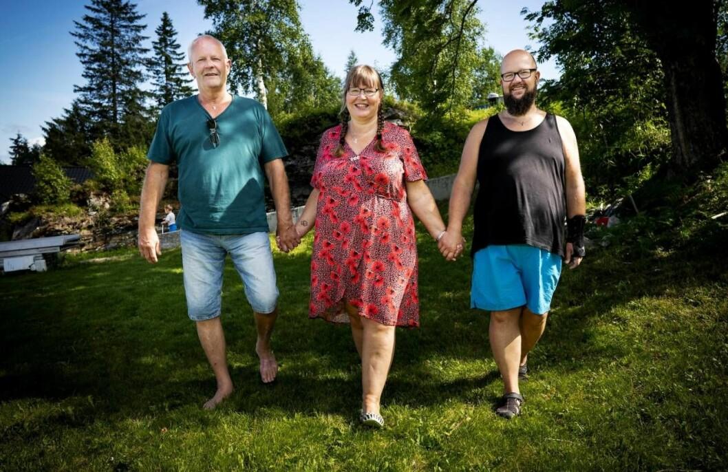 Rita, Wiggo och Tom går hand i hand i ett vackert naturområde
