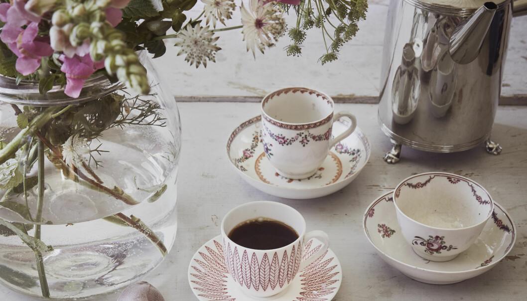 Bord dukat med tre kaffekoppar med fat, stor glasvas med bukett och kaffekaanna.
