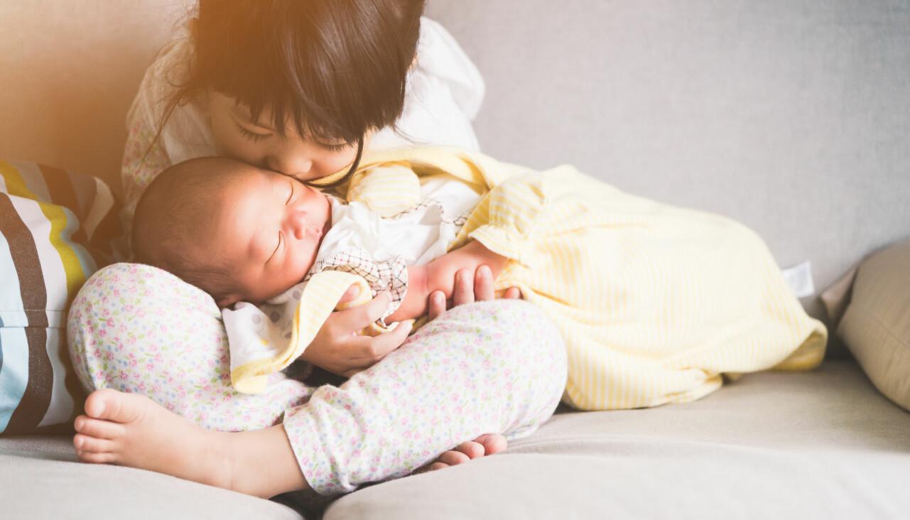Storasyster håller om sitt nyfödda småsyskon.