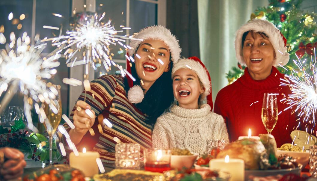 Glad familj firar jul med tomtemössor, julgran och tomtebloss.
