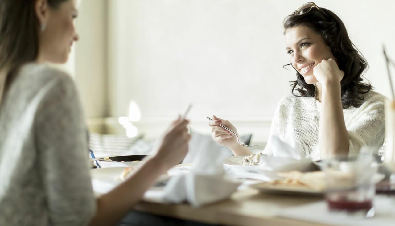 Två kvinnor sitter och pratar vid ett köksbord.