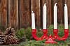 Röd träljusstake som juldekoration på matbordet.