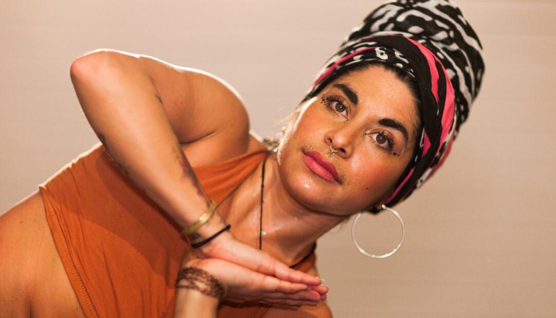 Jaandreé fotad framifrån, ansiktet syns och lite av överkroppen. Hon har bruna ögon och en färgglad turban på huvudet. Hon håller ihop sina handflator.