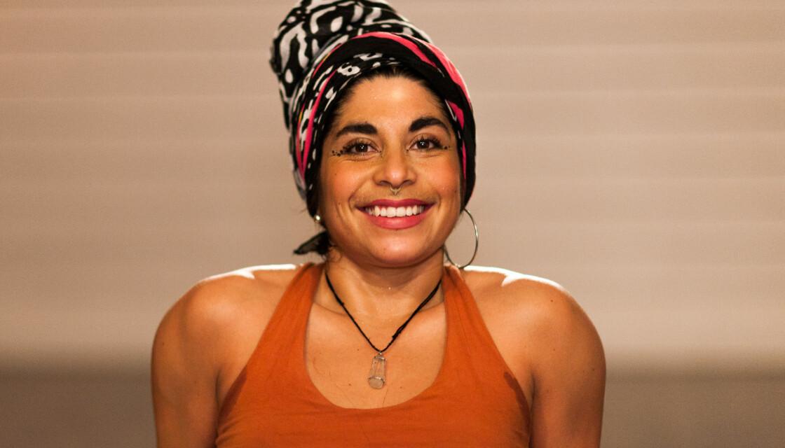 Jaandrée Borelius sitter på golvet och tittar mot kameran med ett leende. Hon har rött läppstift, en färgglad turban på huvudet och ett halsband med en bergskristall runt halsen.