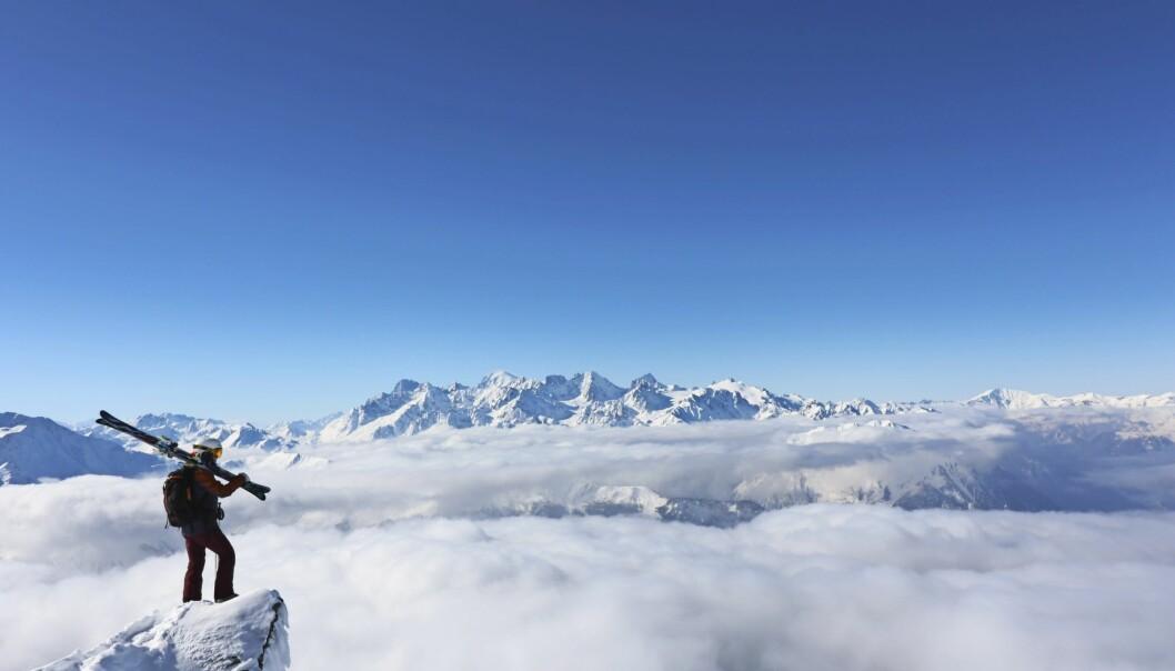 Johanna står längst ut på en klippa med skidor över axeln och blickar ut över alptoppar.