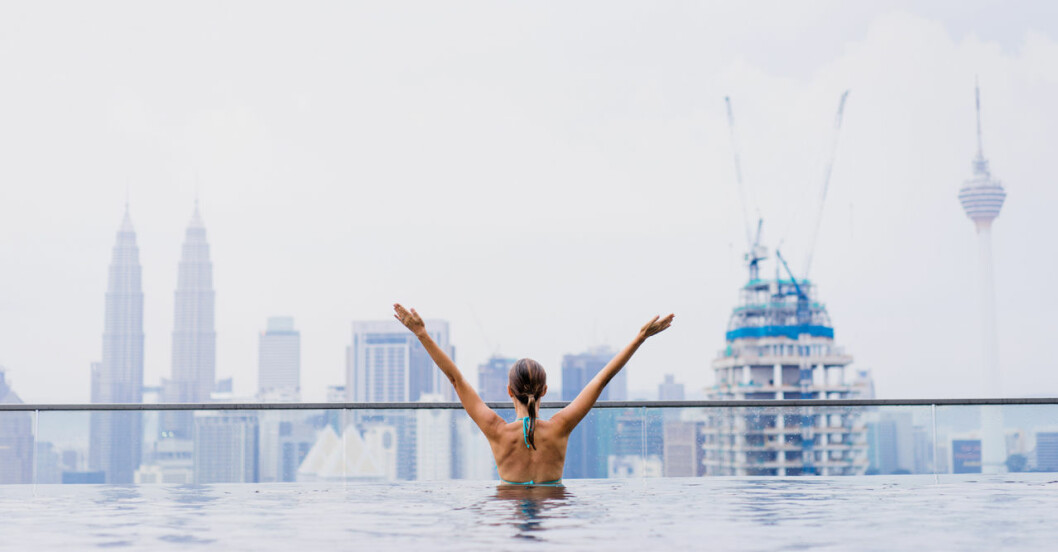 kvinna badar i pool med utsikt