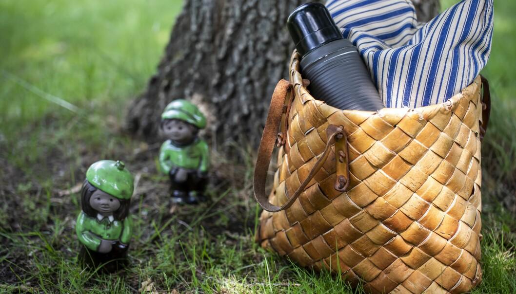 Näverkorg med blåvitrandig kudde och termos i vid ett träd i skogen, bredvid står två gröna och svarta figuriner föreställande en pojke och en flicka.