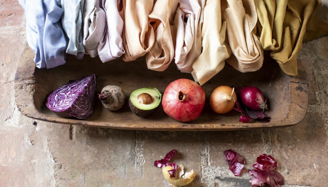 Tyg i olika kulörer tillsammans med rödkål, rödbeta, avokado, granatäpple, dul lök och rödlök på en träskål.