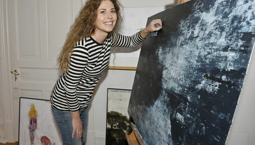 Maria Krall satsar på att måla. Här står hon framför staffliet där en abstrakt tavla i blåskala är placerad.