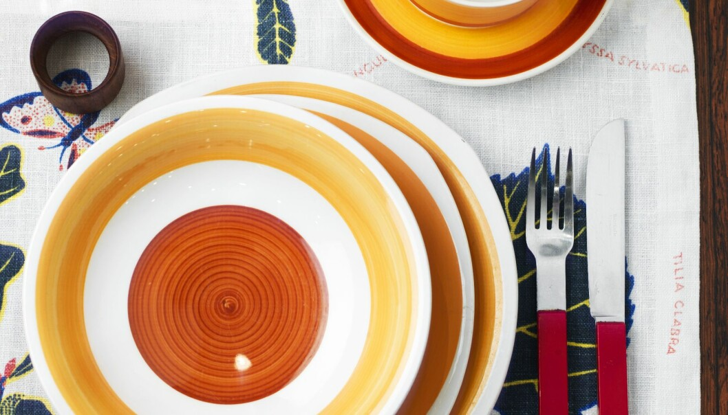 Dukat bord med färgglatt porslin i orange och gula toner.
