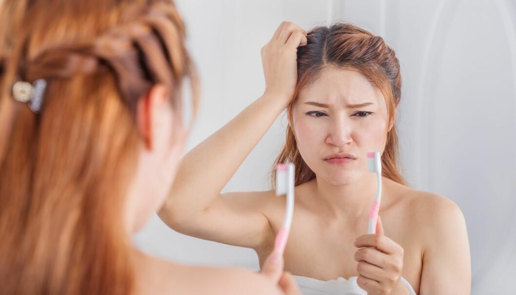 En kvinna tittar på sin tandborste efter att ha insett vilken bakteriehärd den kan vara.