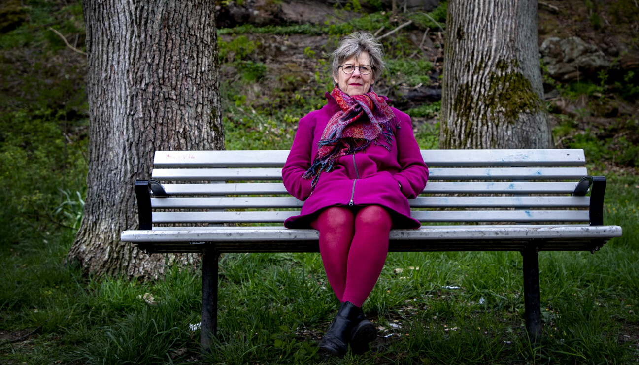 Agnes Wold sitter på en soffa i naturen, klädd i lila och rosa.