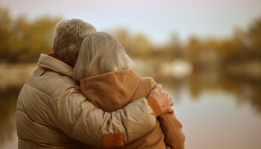 Ett par där mannen är äldre står och tittar ut över en sjö och funderar på vad framtiden har att erbjuda.