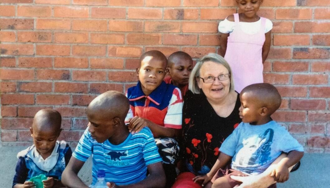Äldre kvinna, Birgitta, sitter med ett gäng barn runt sig, utanför barnhemmet.