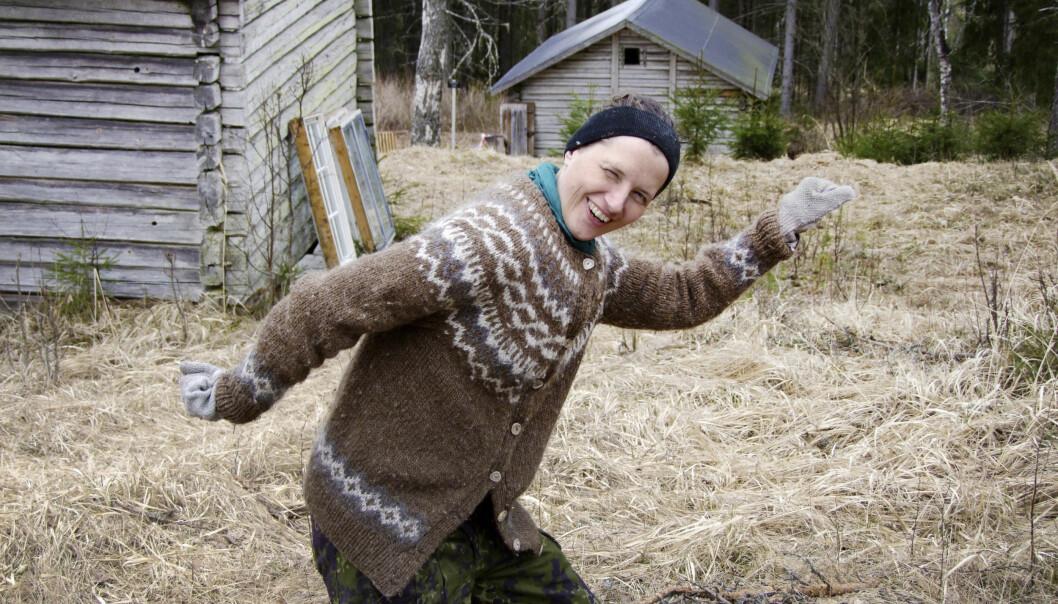 Andrea spexar framför en stuga i skogen.