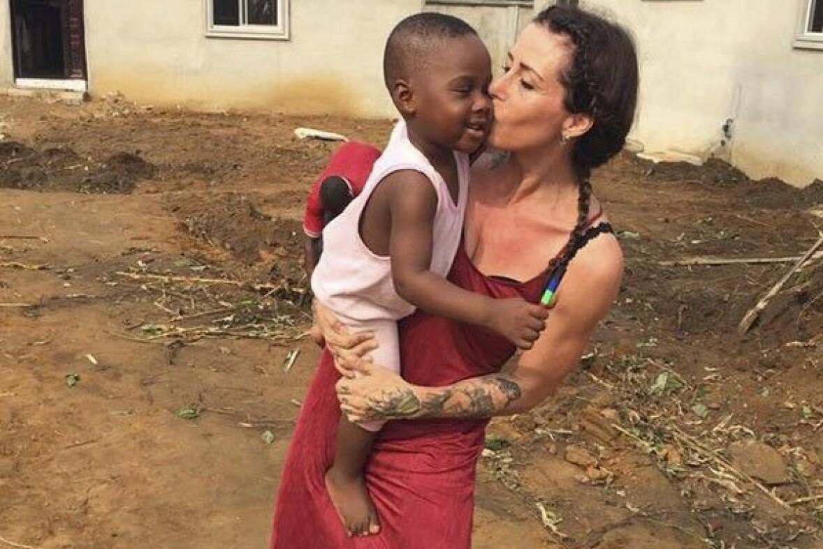 Anja Ringgren Lovén i röd klänning som pussar den glade lille pojken Hope på den runda kinden.
