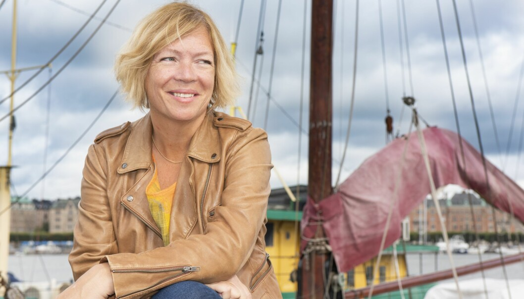 Ann sitter i hamnen i Stockholm och bakom henne syns båtar och hus.