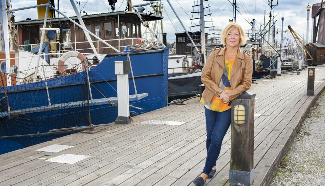 Ann står i hamnen framför några gamla båtar, lutar sig mot en lampa och berättar om hur hon sa upp sig och gav sig ut på långsegling med sin man.