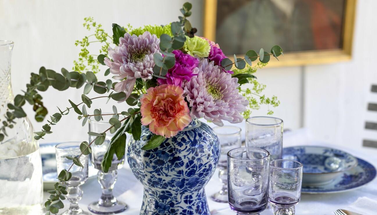 Bord dukat i gustaviansk stil med blåvit servis och kruka med stor blombukett.