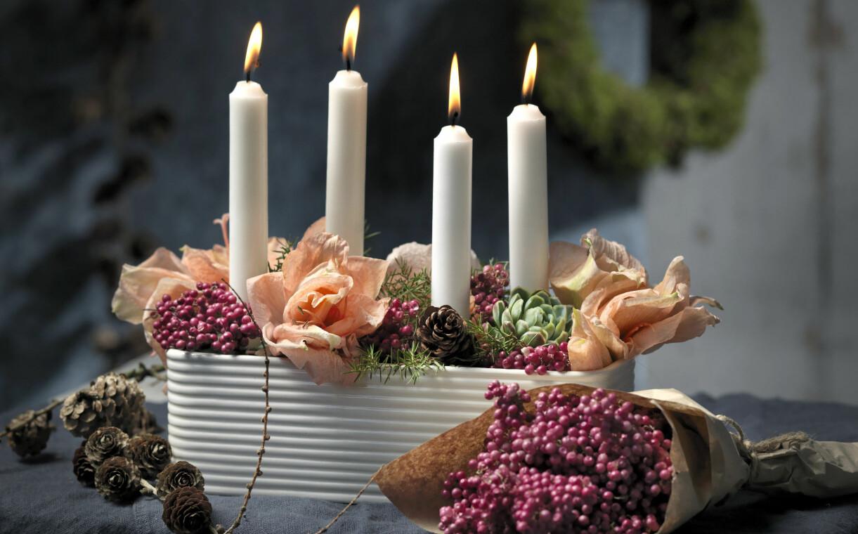 Arrangemang med torkad amaryllis och levande ljus.