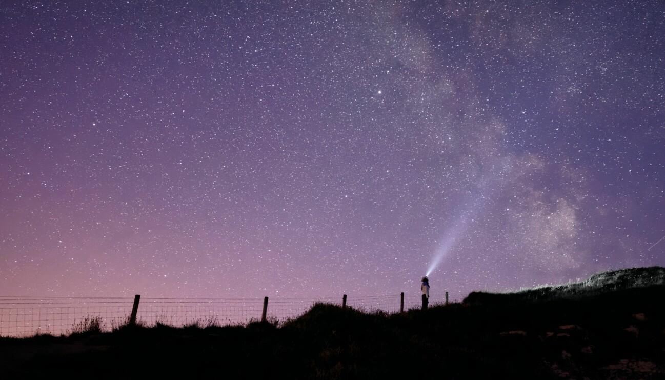 En kvinna som tittar upp mot stjärnorna och undrar vad hon kan vänta sig av sitt horoskop 2021.