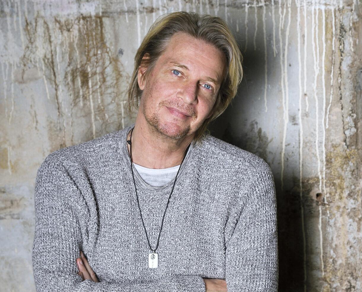 Artisten Tommy Nilsson, med en sliten betongvägg i bakgrunden, blickar framåt, och ser tillbaka på sitt liv och sin karriär.