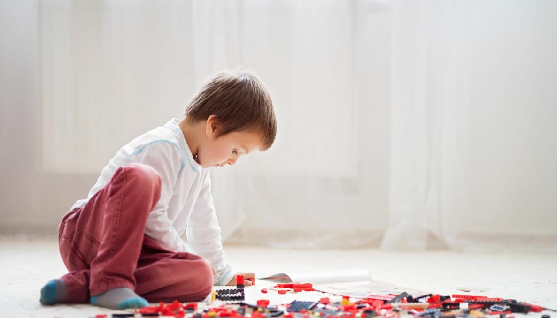 Liten pojke som troligtvis har autistiska drag sitter på golvet och leker koncentrerat med lego.