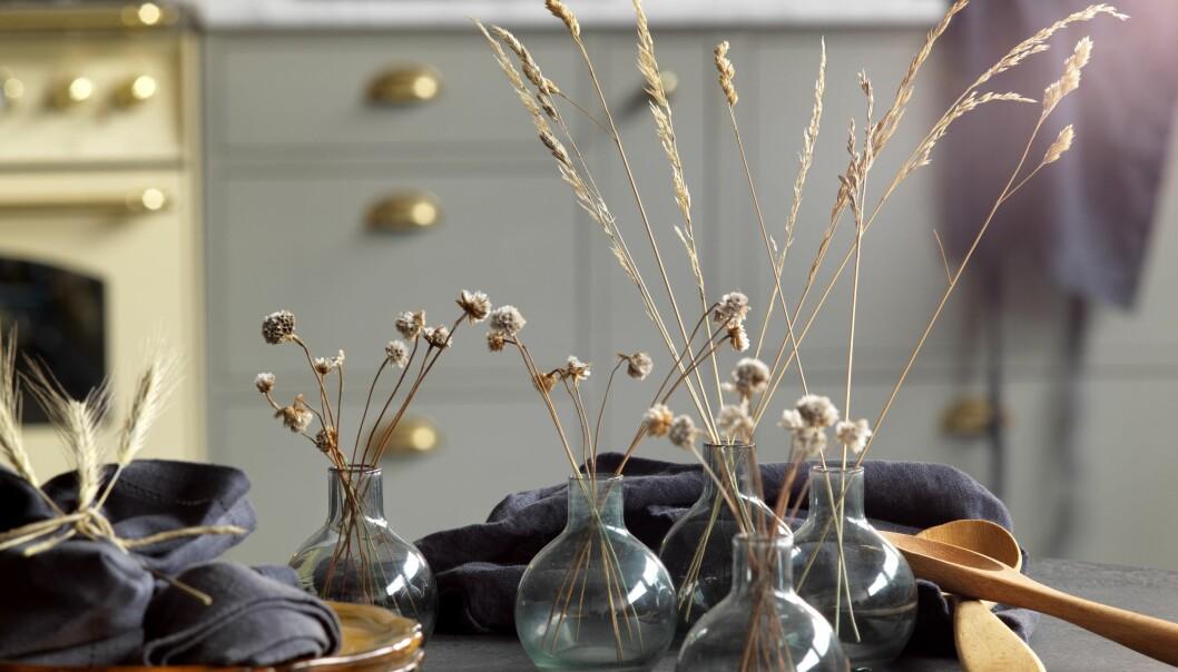 Små glasvaser med torkade blommor i.