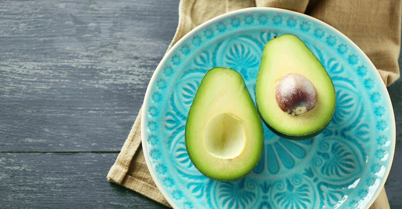 Delad avokado på en blå tallrik.