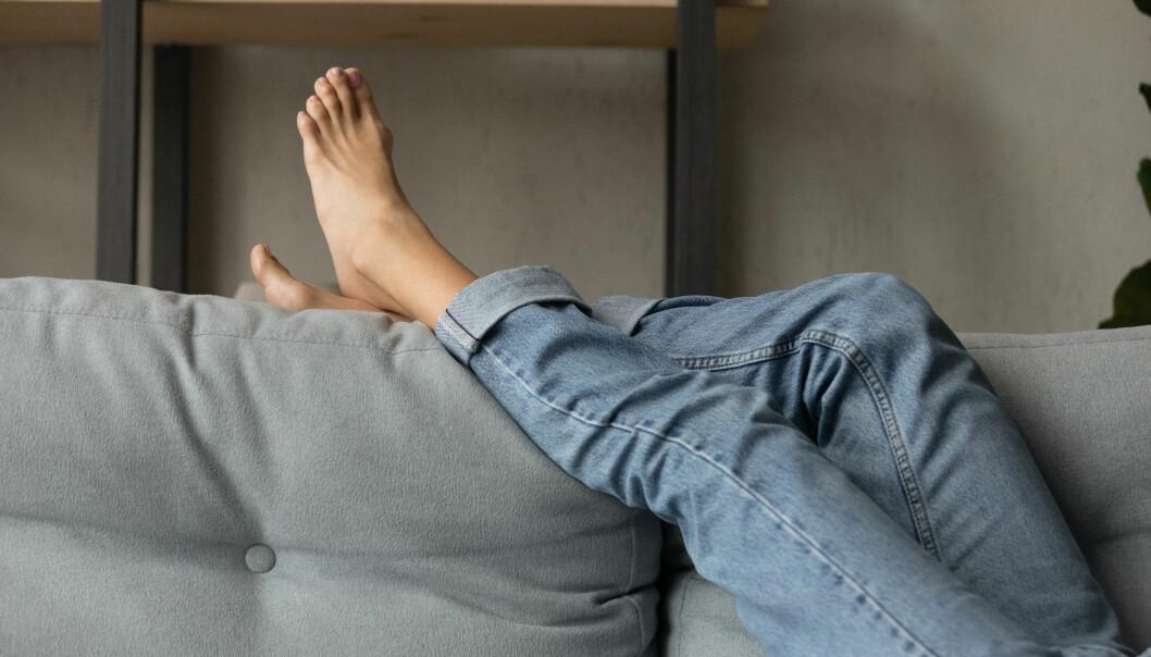 Barfotafötter i en soffa