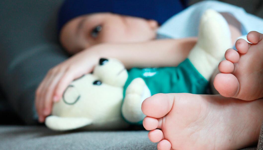 Ett barn med cancer som ligger uppkrupet i sängen.