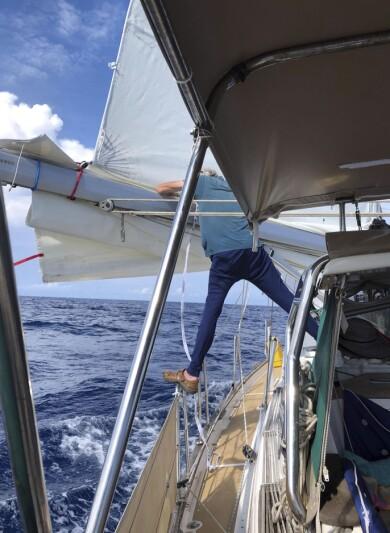 Båten är ute till havs och Mats står i aktern och ordnar med seglet.