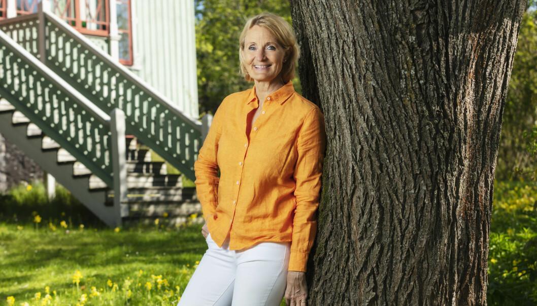 Sommar i P!-producenten Bibi Rödöö lutar sig mot en gammal trädstam.