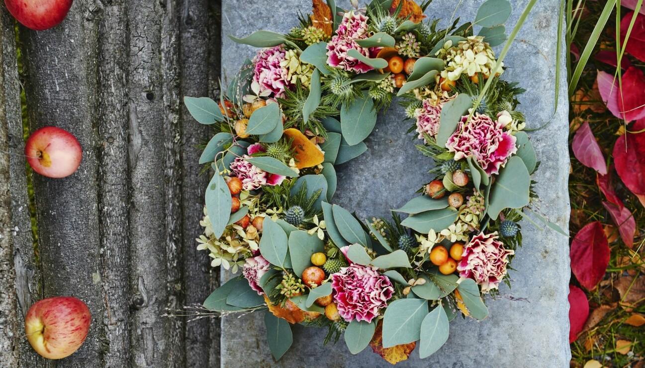 Bild på en krans med olika blad, torkade blommor och bär på en stenbakgrund. Till höger finns röda löv och till vänster finns äpplen i en rad.