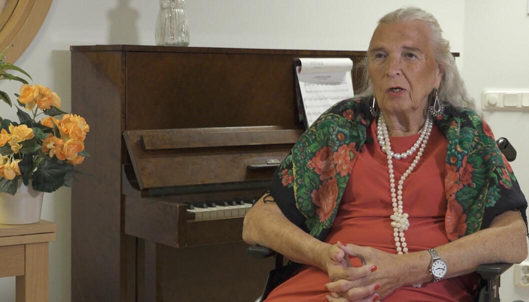 Birgitta Lundberg sitter i rullstol framför ett piano.