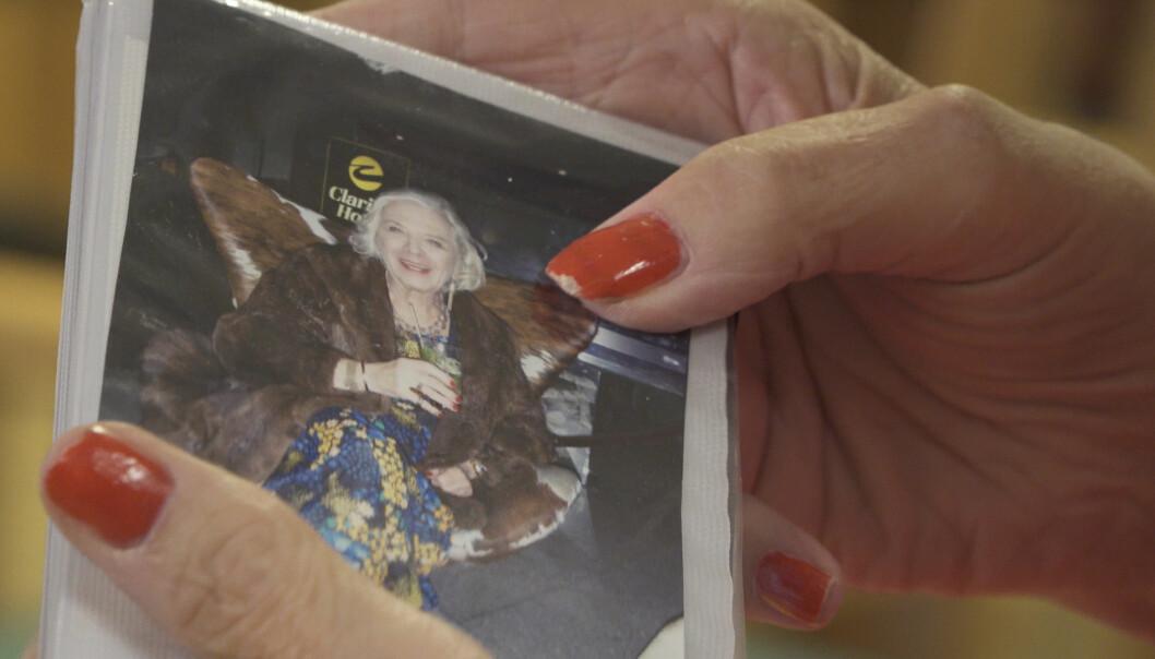 Birgitta Lundberg visar ett foto av sig själv i klänning och pälskappa.