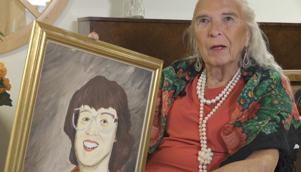 Birgitta Lundberg visar upp en oljemålning av hustrun Inger.
