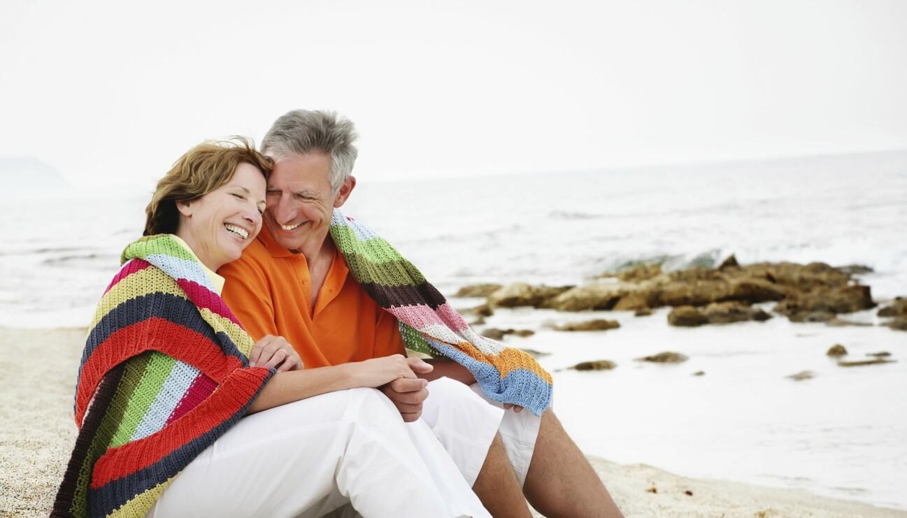 Ett medelålders par sitter på en strand nära varandra under en filt.