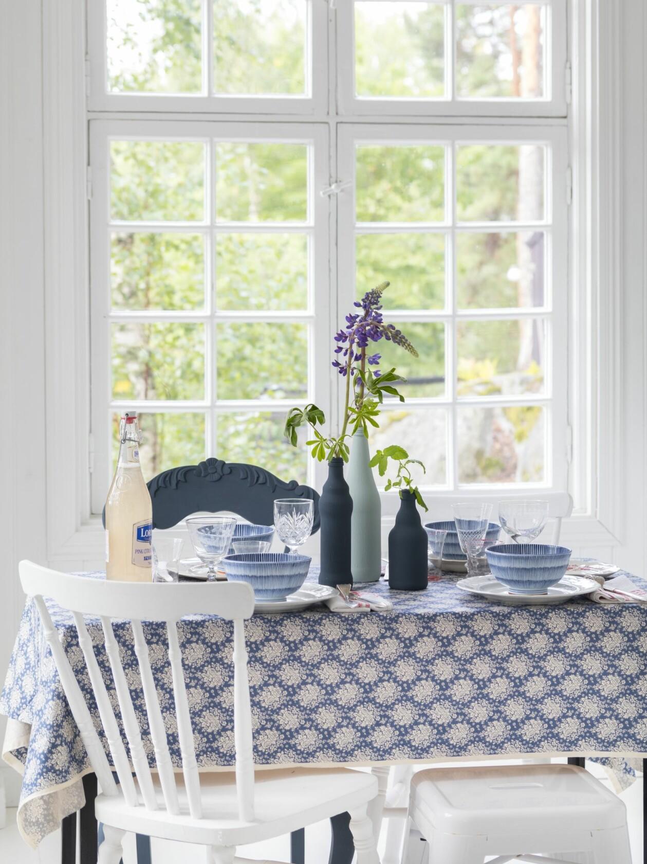 Blåvitt kök med stort fönster i bakgrunden