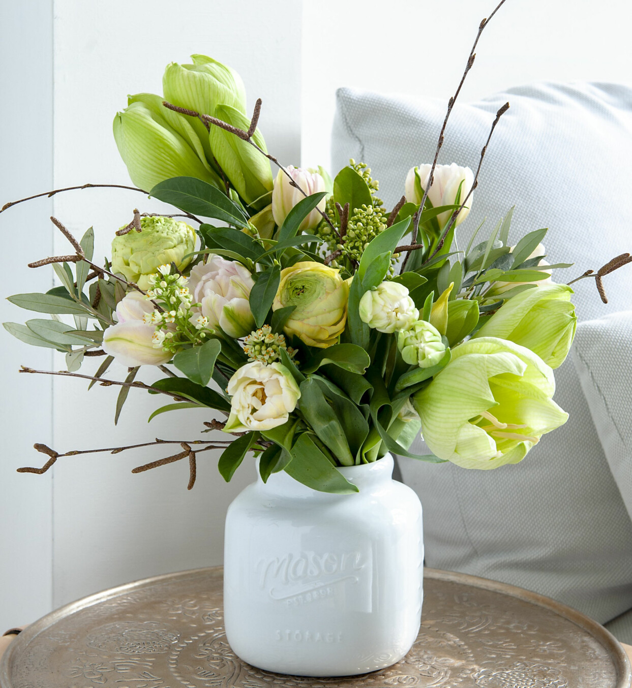 Bukett i gröna och vita toner med tulpaner, amaryllis, kvistar och ranunkler.