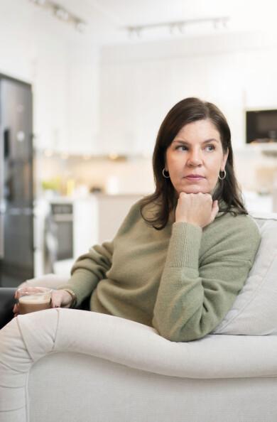 Camilla Jonsson, vars man dog i bröstcancer, sitter i en soffa och berättar om sorgen och ensamheten.
