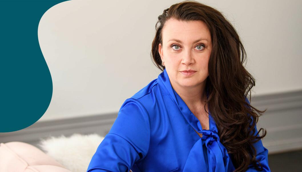 Camilla Läckberg sitter i en soffa och tittar allvarligt in i kameran.