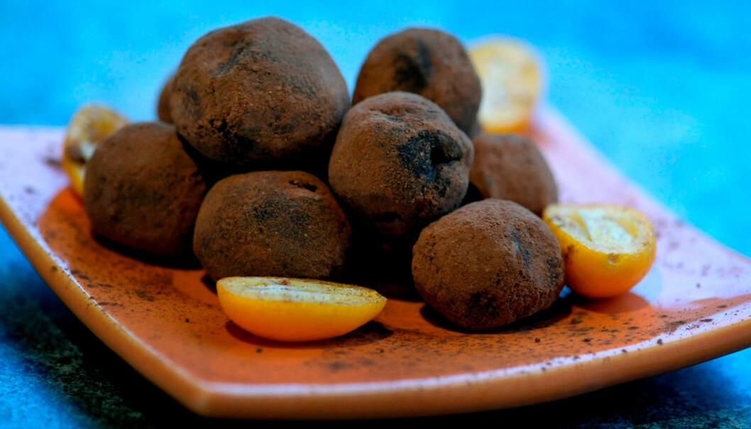 Runda chokladtryfflar och gula tomater på ett fat.